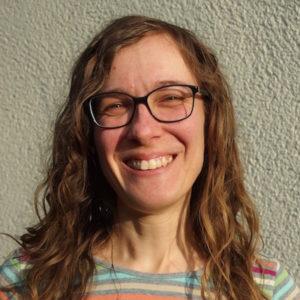 Porträtfoto von Birthe zur Nieden. Sie hat langes, welliges Haar, trägt eine Brille und ein bunt geringeltes T-Shirt und lacht in die Kamera